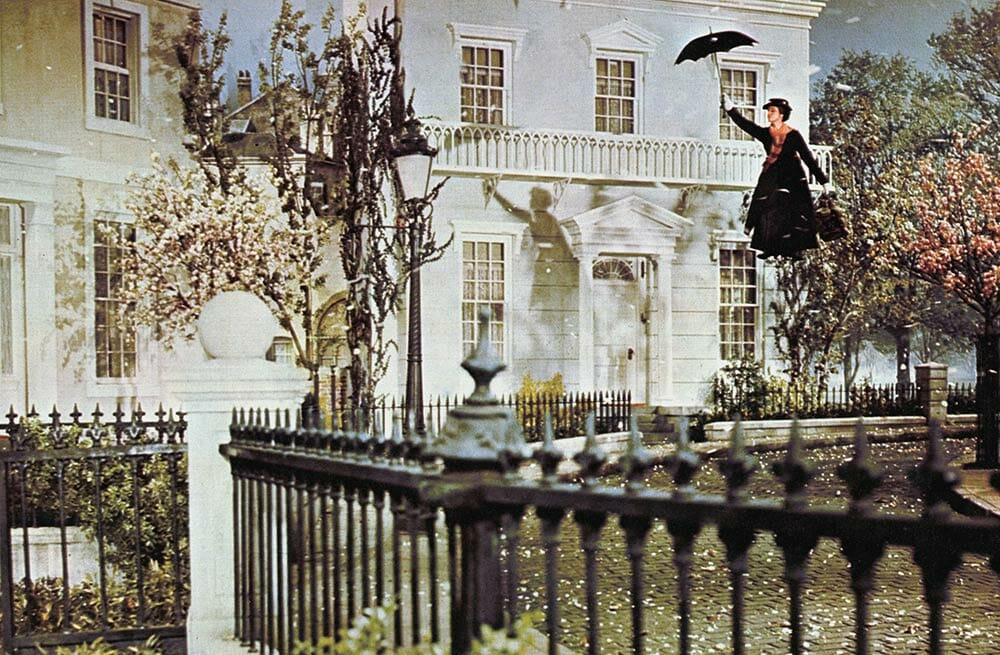 Mary Poppins flying in front of a mansion