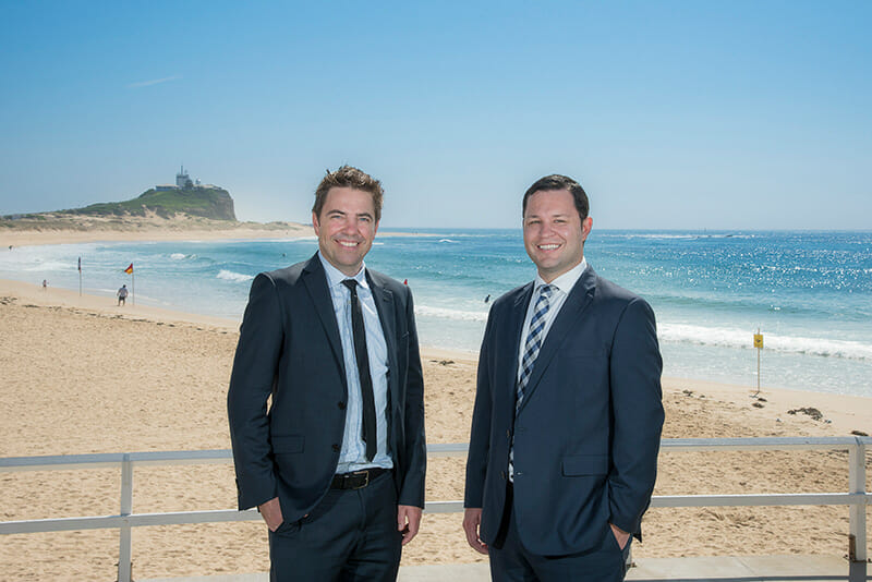 Sommerville Legal's Stephen Lynch and Elliot standing near the seafront